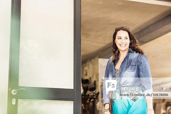 Frau im Jeanshemd schaut lächelnd weg