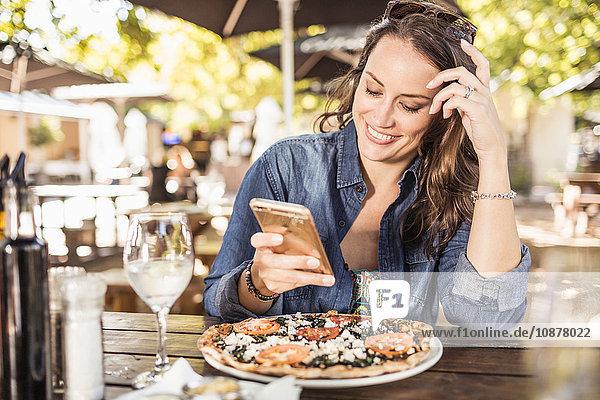 Frau im Bürgersteig-Café schreibt SMS auf Smartphone