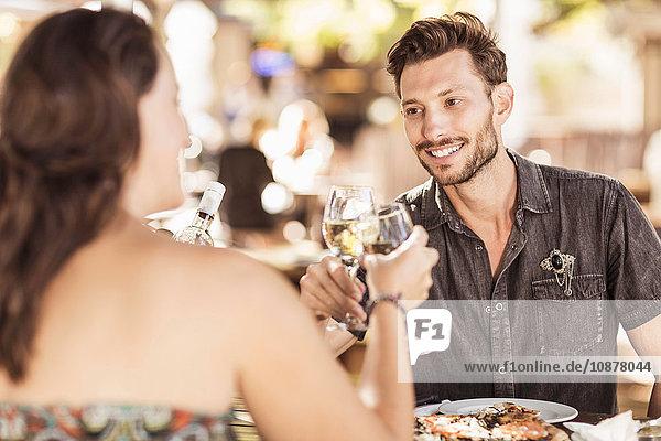 Ein Paar isst im Straßencafé und bringt einen Toast aus