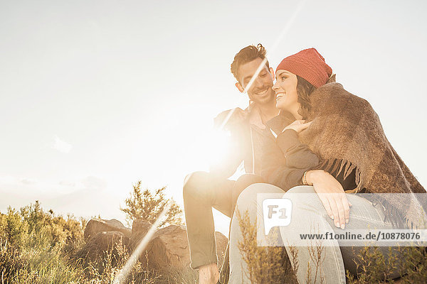 In eine Decke gehülltes Ehepaar sitzt auf einem Felsen im Feld