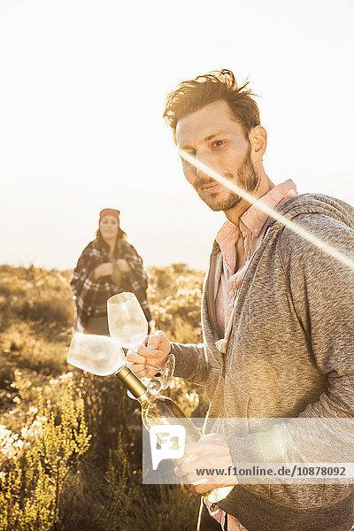 Mann im Feld hält Weinflasche und Weingläser in der Hand und schaut lächelnd in die Kamera