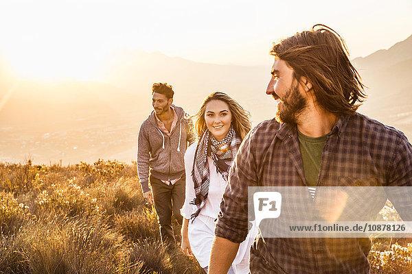 Freunde wandern lächelnd über das Grasland