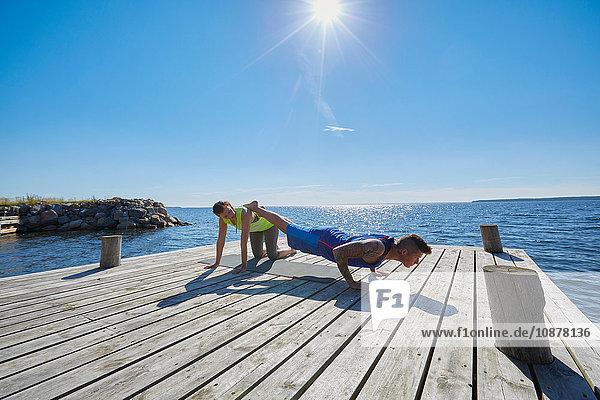 Mann auf dem Pier macht Liegestütze  Beine auf Freund erhoben