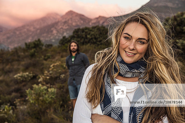 Woman and friend on hillside looking at camera
