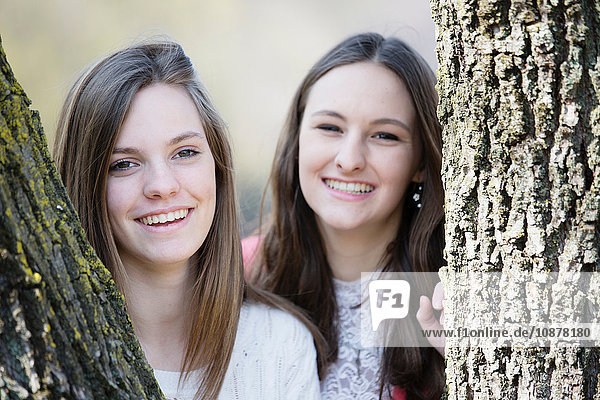 Portrait of female friends behind tree trunks looking at camera smiling