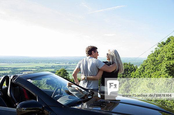 Älteres Paar sitzt auf einem Cabriolet und schaut sich die Aussicht an