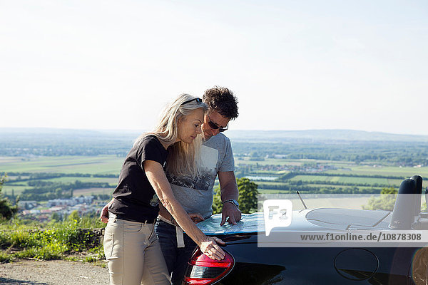 Mature couple looking at map on car boot