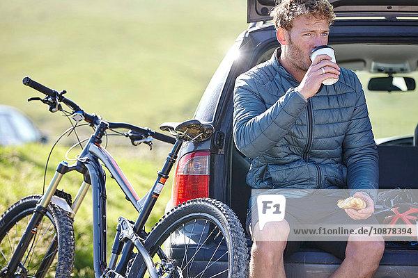 Radfahrer sitzt im Kofferraum eines Autos und trinkt aus Einwegbecher