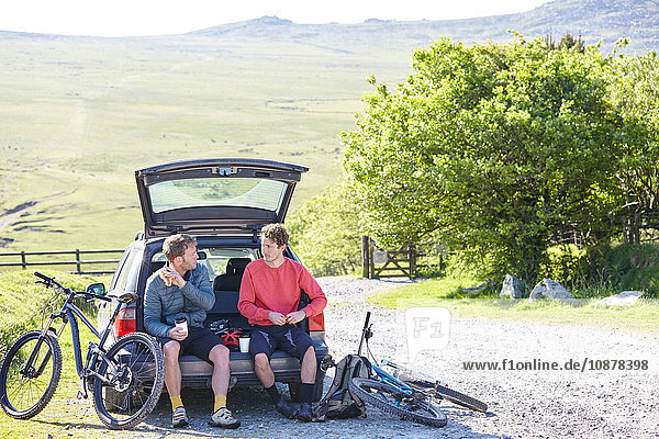 Cyclists sitting on car boot taking a break
