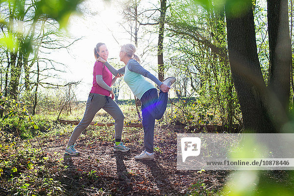 Side view of women in forest face to face holding ankle stretching leg