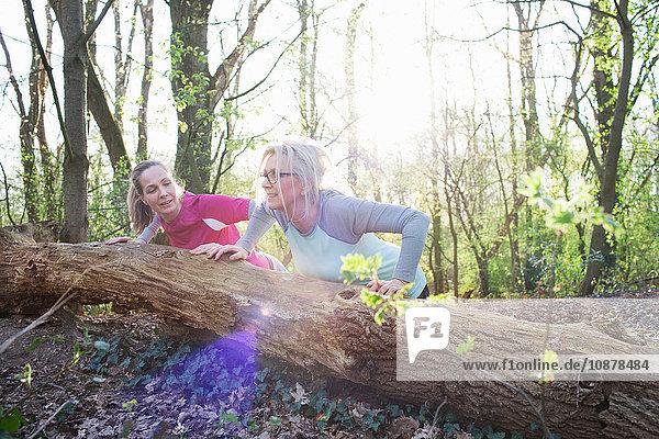 Women in forest doing press ups against fallen tree