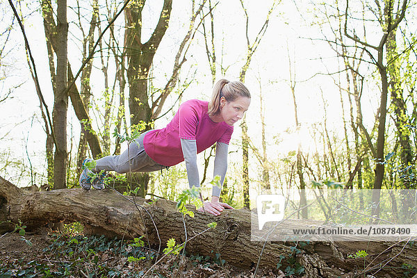 Woman in forest doing press ups on fallen tree