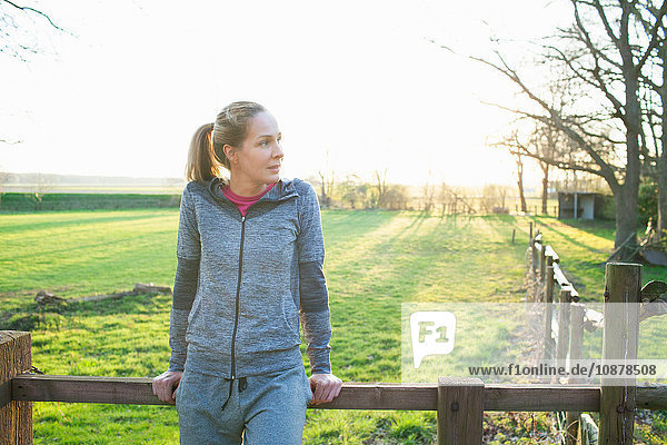 Woman wearing sports clothing leaning against fence looking away