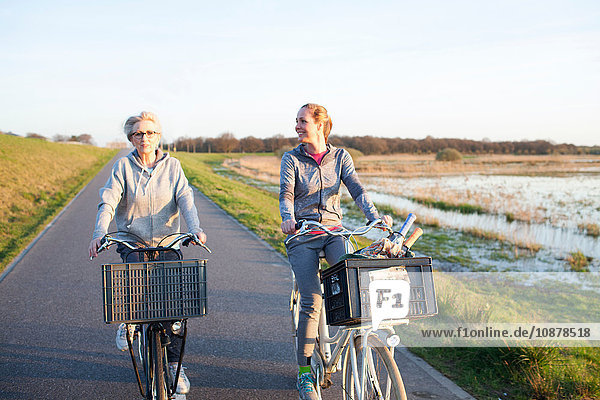 Front view of women cycling on path by marshland smiling