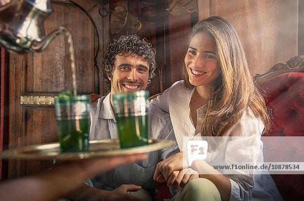Junges Paar im Riad  dem Getränke auf Tablett serviert werden  Marrakesch  Marokko