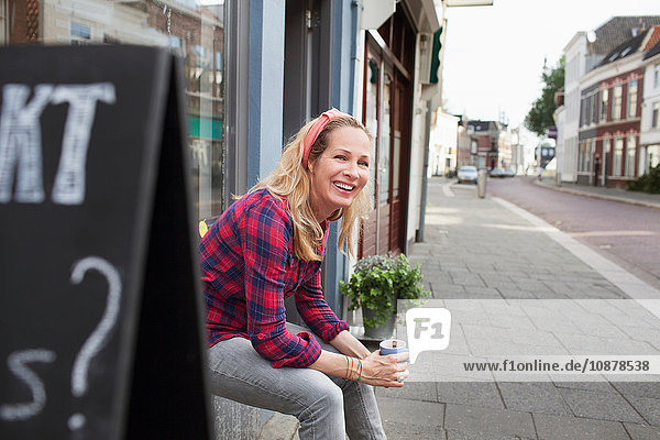 Woman sitting on shop windowsill holding coffee cup looking away smiling