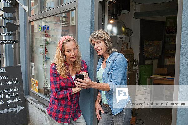 Women standing in shop doorway looking at smartphone