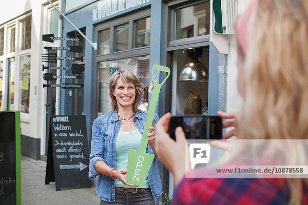 Friend photographing woman in front of shop holding open sign
