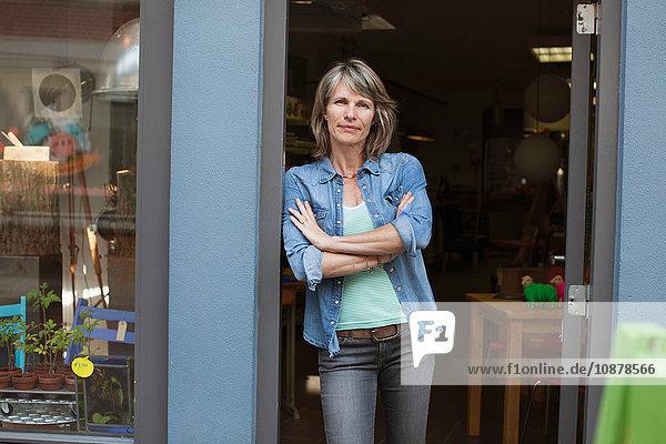 Woman in shop doorway  arms crossed looking at camera