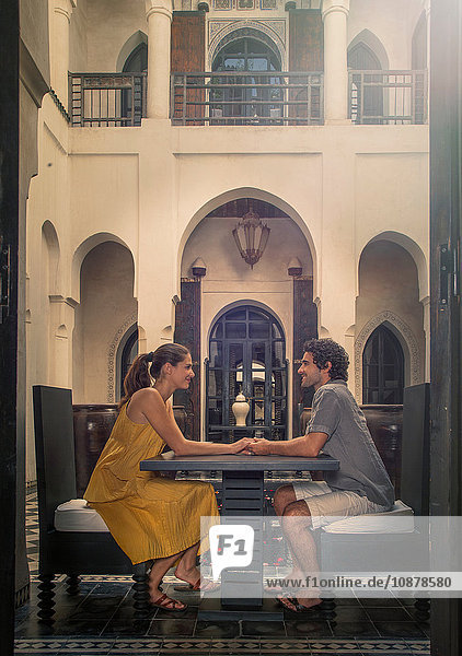 Side view of young couple at table face to face holding hands  Marrakesh  Morocco