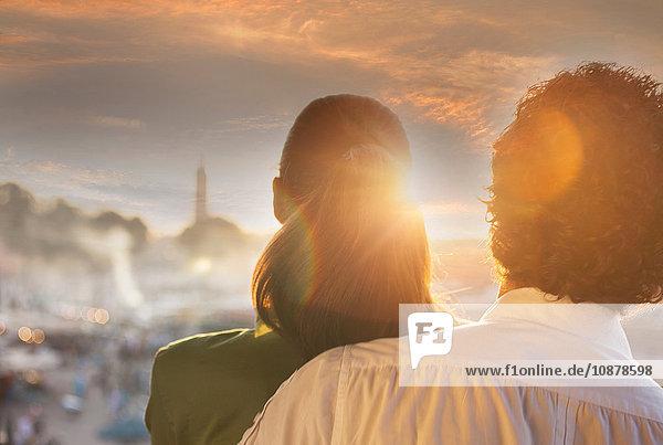 Rückansicht eines Paares  das den Sonnenuntergang über dem Jemaa el-Fnaa-Platz bei Sonnenuntergang betrachtet  Marrakesch  Marokko