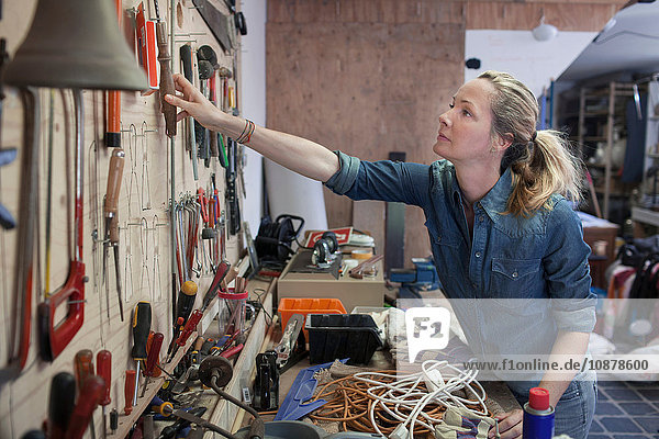 Woman in workshop reaching for tools hung on wall