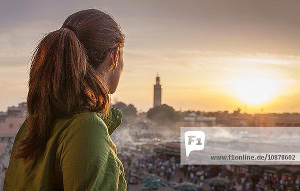 Rückansicht einer Frau  die den Sonnenuntergang über dem Platz Jemaa el-Fnaa  Marrakesch  Marokko  betrachtet Rückansicht einer Frau, die den Sonnenuntergang über dem Platz Jemaa el-Fnaa, Marrakesch, Marokko, betrachtet