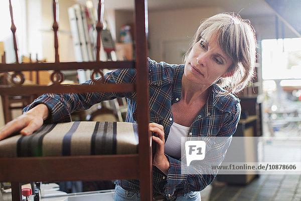 Woman in workshop examining chair
