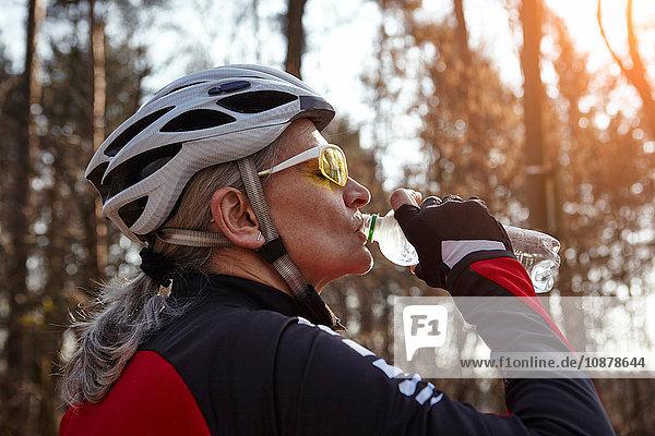 Seitenansicht einer Frau mit Fahrradhelm und Sonnenbrille  die Wasser aus einer Plastikflasche trinkt