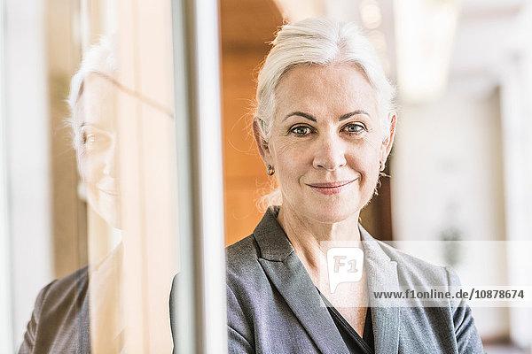 Geschäftsfrau lehnt an Glastür und schaut lächelnd in die Kamera