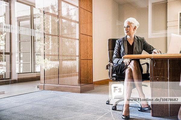 Blick durch das Glas einer Geschäftsfrau  die an einem Schreibtisch sitzt und mit gekreuzten Beinen wegschaut