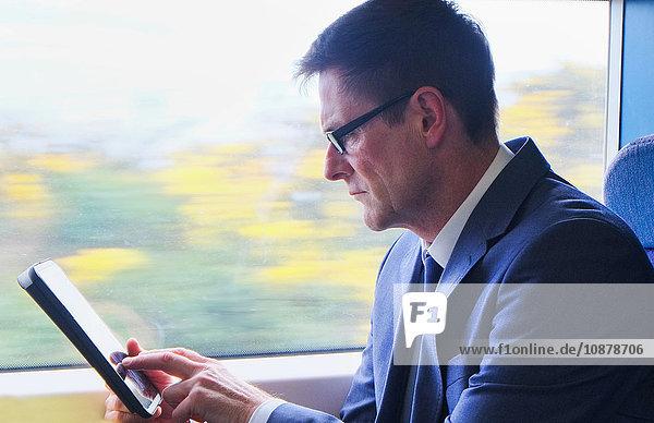 Ein reifer Geschäftsmann sitzt im Zug und verwendet ein digitales Tablet