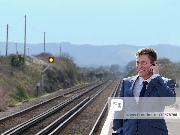 Ein reifer Geschäftsmann steht auf dem Bahnsteig und benutzt ein Smartphone