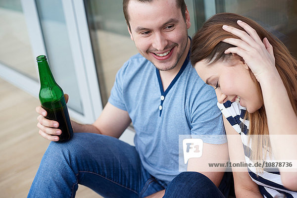 Junges Paar sitzt im Freien und trinkt Flaschenbier