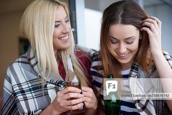 Zwei Freundinnen sitzen im Freien und trinken Flaschenbier