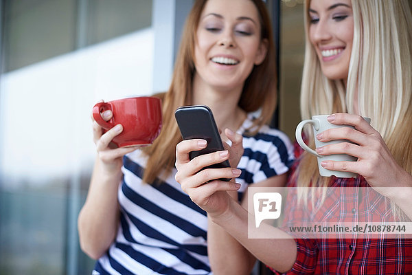 Two female friends  drinking coffee  outdoors  looking at smartphone