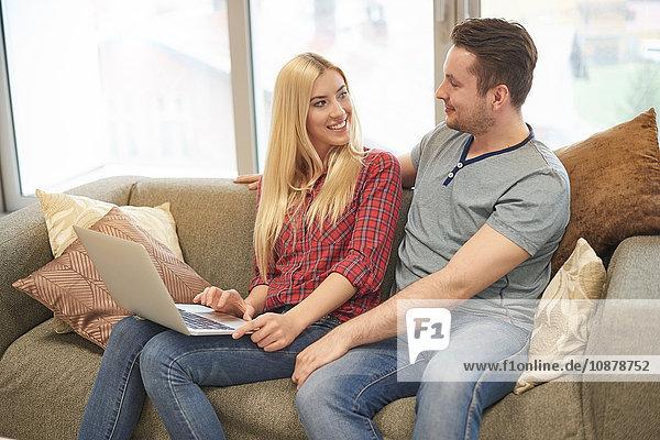 Junges Paar zu Hause  auf dem Sofa sitzend  mit Laptop