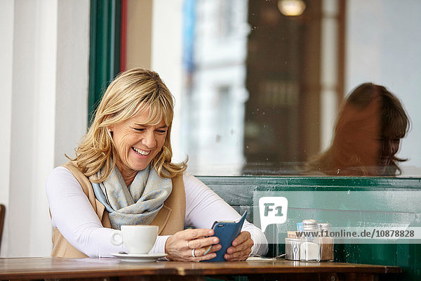 Mature woman reading smartphone text at sidewalk cafe table