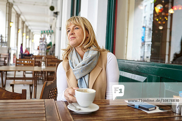 Mature woman looking out from sidewalk cafe table