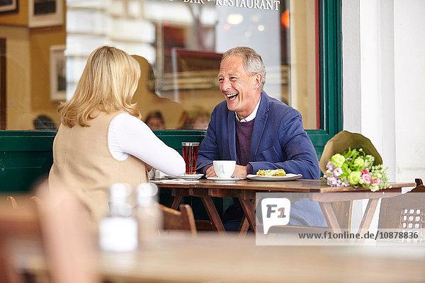 Reifes Paar beim Date lacht gemeinsam am Tisch im Straßencafé
