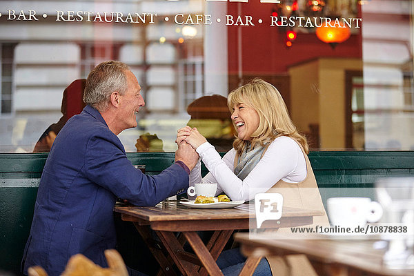 Mature dating couple holding hands at sidewalk cafe table