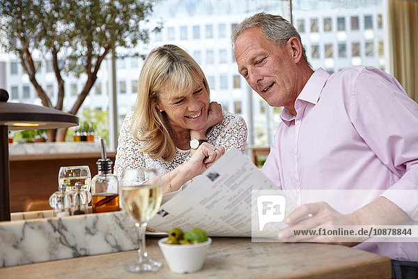 Reifes Dating-Paar liest Speisekarte am Restauranttisch