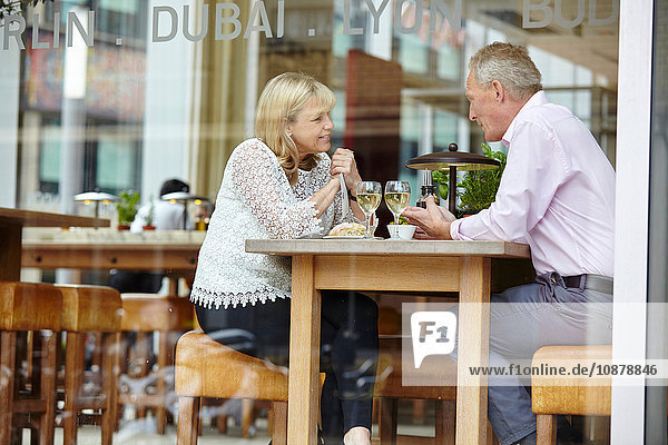 Window view of mature dating couple chatting at restaurant table