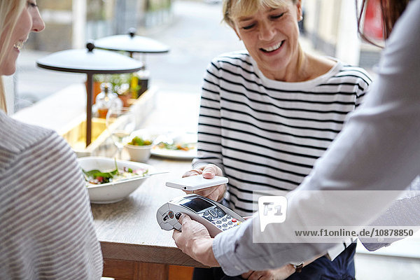 Woman using smartphone contactless payment at restaurant table  London  UK