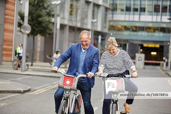 Älteres Pärchen  das lacht  während es auf Leihfahrrädern Fahrrad fährt  London  UK