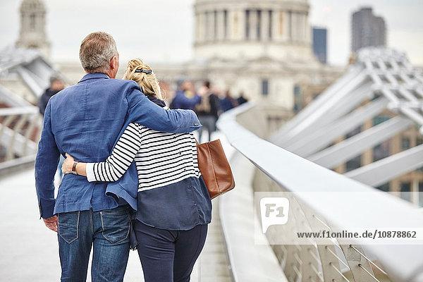 Rückansicht eines reifen Liebespaares beim Überqueren der Millennium Bridge  London  UK