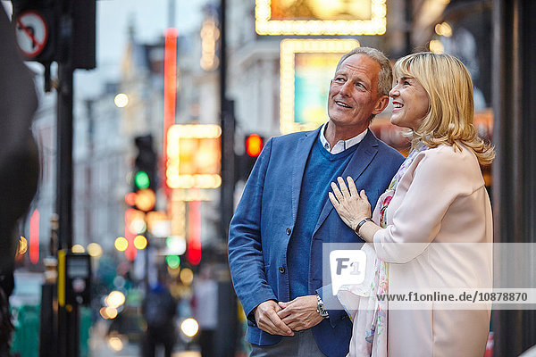 Mature dating couple looking up from city street at dusk  London  UK