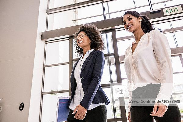 Junge Geschäftsfrauen kommen am Büroeingang an