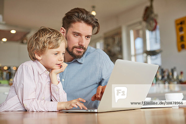 Father and son using laptop in home office
