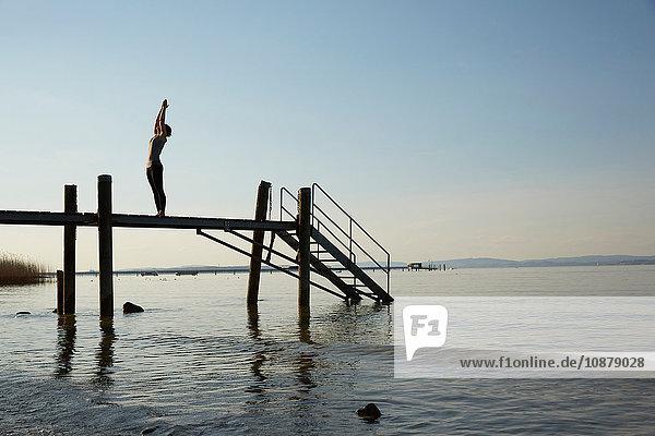Silhouette einer Frau auf den Pfeilerarmen in Yogastellung erhoben